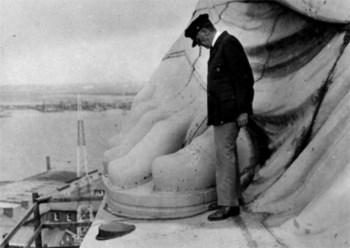 Um homem junto ao pé da estátua