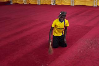 Um voluntário varre o tapete antes da chegada de Bento XVI