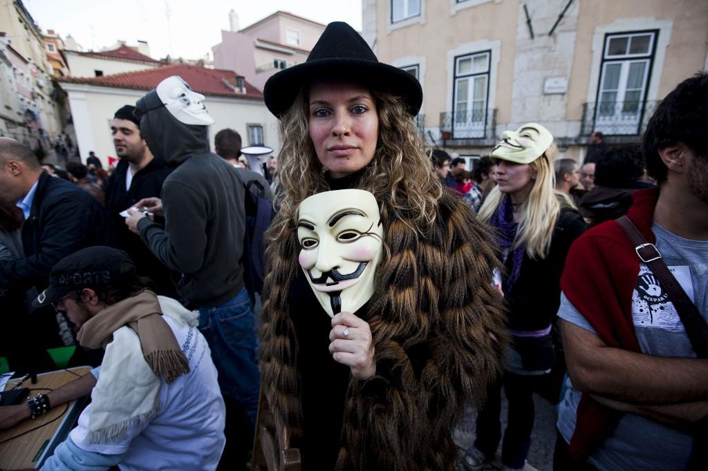 No dia da greve geral, manifestantes em frente ao Parlamento usam uma máscara associada ao grupo de hackers Anonymous