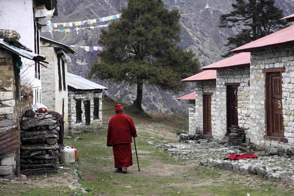 Um monge  caminha ao longo dos dormitórios dos monges mais jovens na aldeia Tengboche nos Himalaias  (no leste do Nepal)