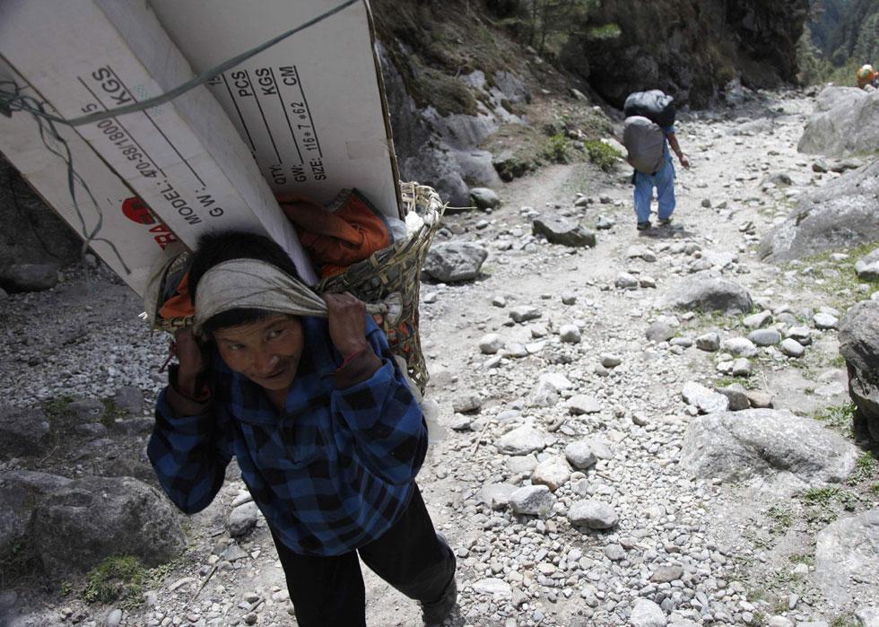 Um nepalês caminha com a sua carga perto de Phakding no leste do Nepal