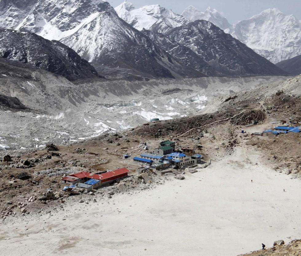 Um turista caminha por Gorak Shep com o glaciar Khumbu como pano de fundo