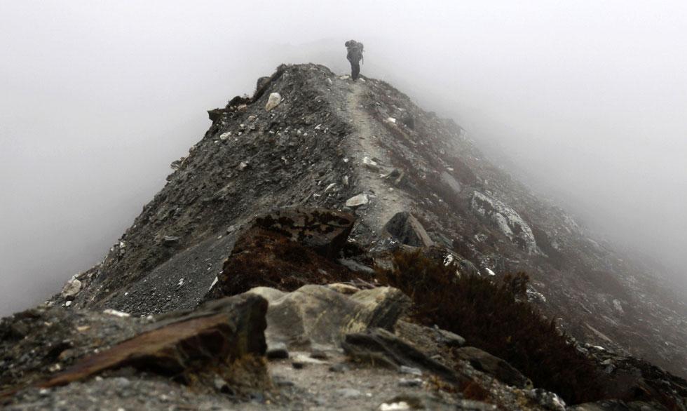 Um nepalês caminha com sua carga ao longo de um caminho no cume da montanha perto da vila Chukung no Nepal