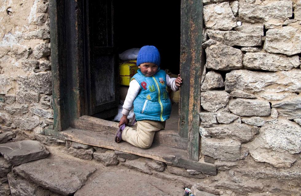 Um rapaz posa em frente da sua casa na aldeia Namche Bazar nos Himalaias
