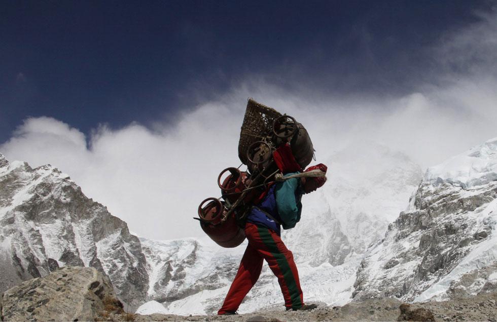 Um nepalês caminha com a sua carga vindo do acampamento de Evereste