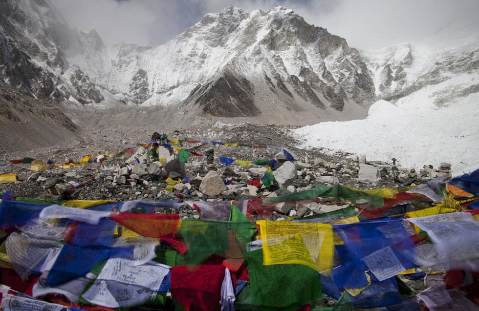 Bandeiras de oração budista flutuam ao vento com o acampamento de Evereste visto ao fundo