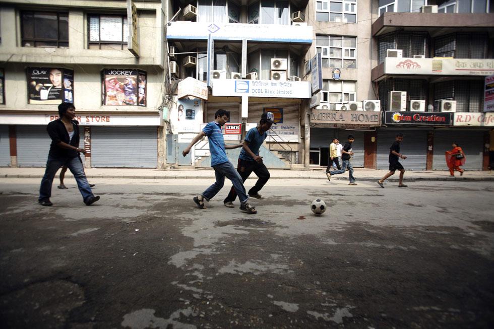 Jovens jogam futebol numa rua de Katmandu