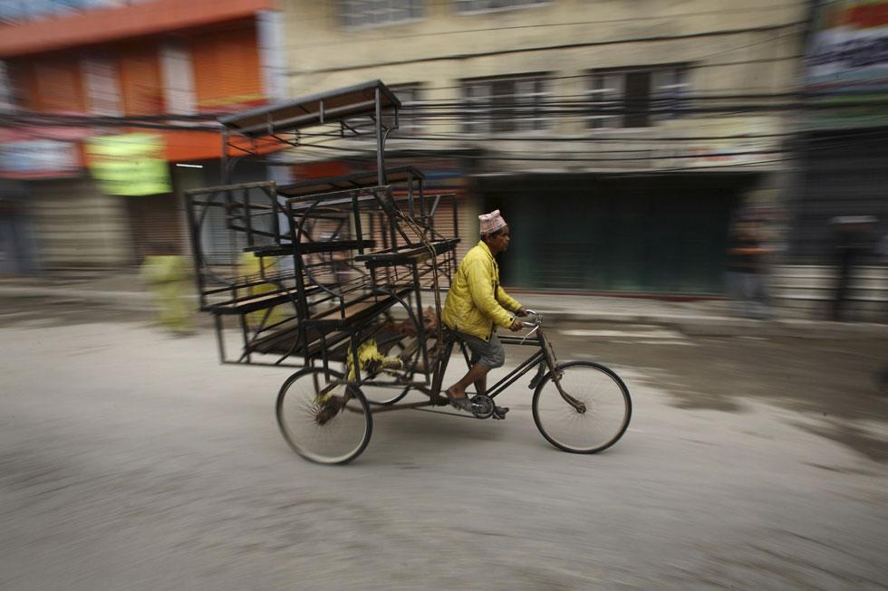 Homem transporta mercadorias na sua trishaw em Katmandu