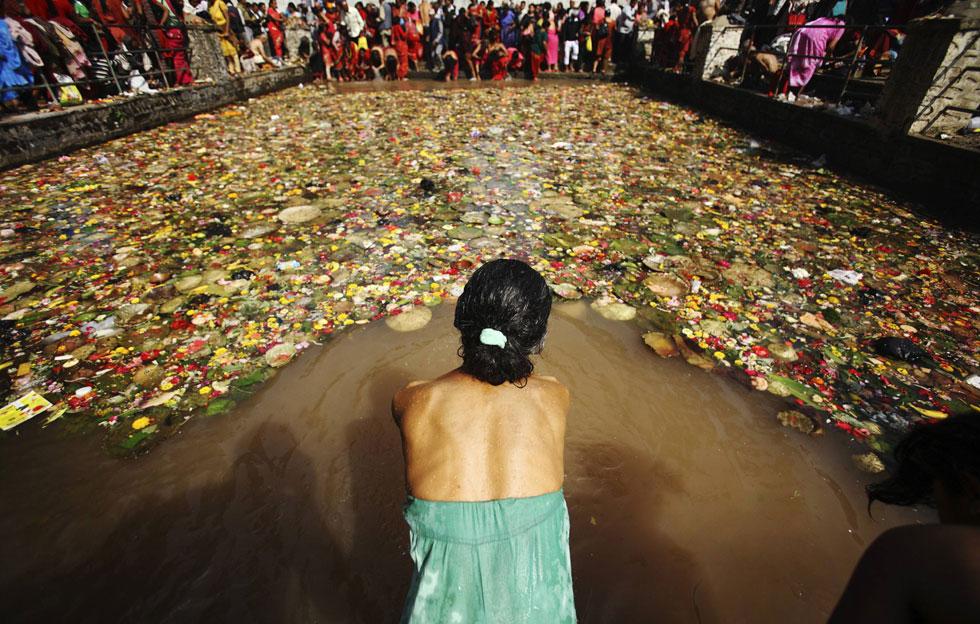 Uma devota prepara-se para o mergulho sagrado no Matathirtha no Dia das Mães em Katmandu