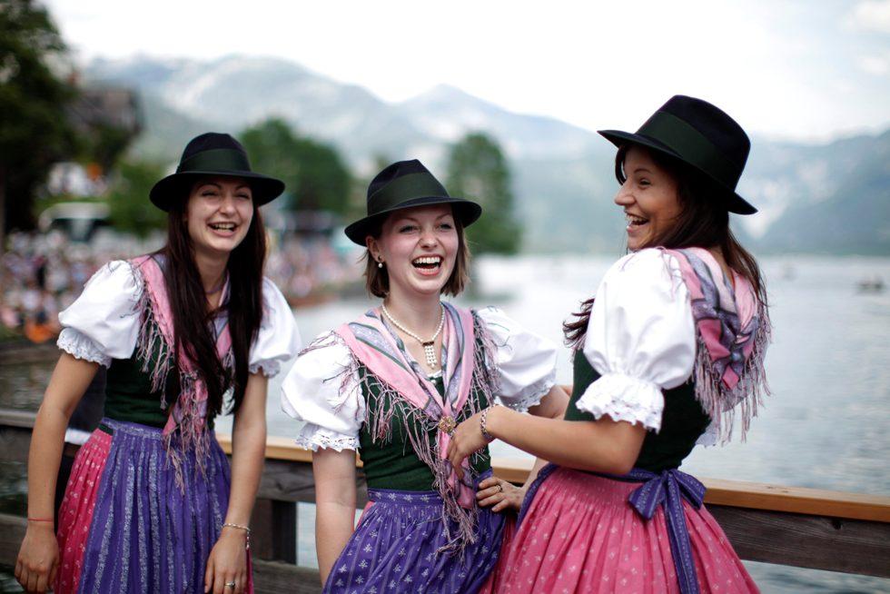 Algumas raparigas assistem ao desfile de barcos junto ao lago Grundlsee nos seus vestidos tradicionais Dirndl