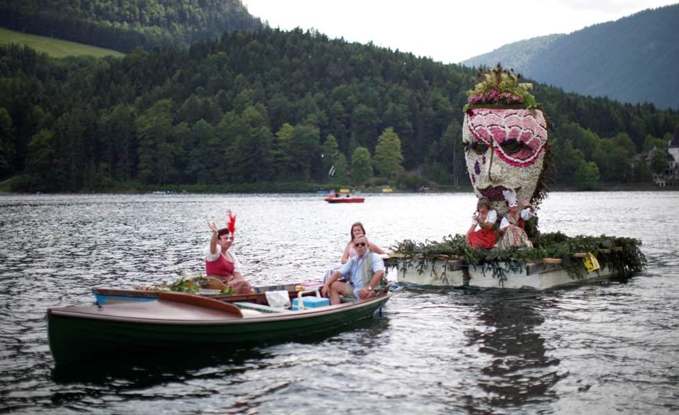 Um barco decorado com uma máscara de carnaval desfila no lago Grundlsee