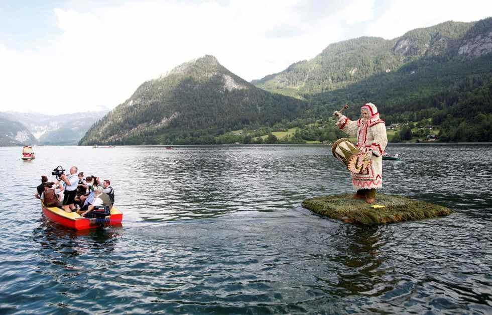 Um barco decorado com uma máscara de carnaval tradicional da região desfila no lago Grundlsee. A figura foi a vencedora da competição no desfile de carros