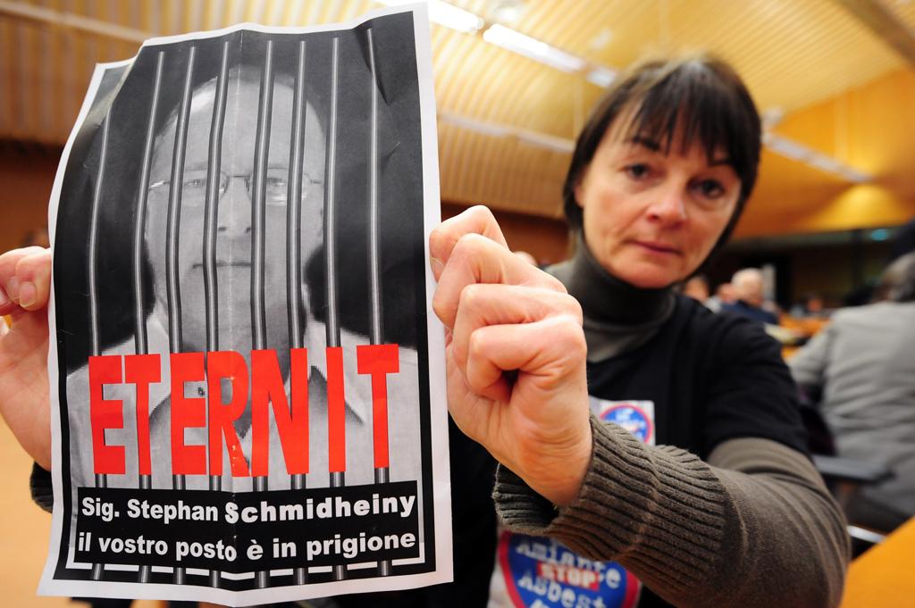 Mulher segura cartaz em que se lê
