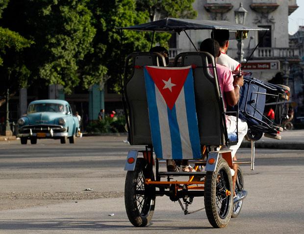 Táxi a pedal engalanado com bandeira cubana