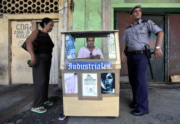 Relojoeiro nas ruas de Havana com barraca bem decorada. No poster central, entre modelos,  lê-se: ´Hoy es un día maravilloso. Usted verá como ahorita viene alguién y lo jode´