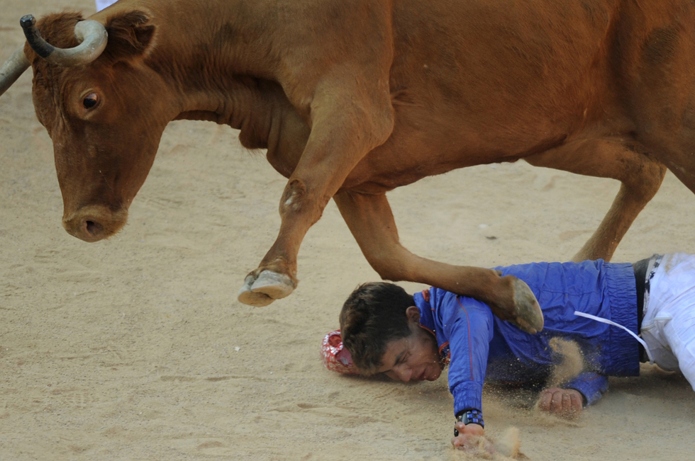 Um participante é pisado por uma vaca selvagem na praça de touros após o início da segunda corrida de touros de San Fermin