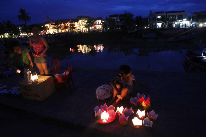 Vietname, Hoi An | Vendedores de velas e lanternas na margem do rio Hoai em Hoi An, Património da Humanidade pela Unesco. Nos dias 14 de cada mês lunar, o Governo encoraja os habitantes e visitantes a usarem velas e lanternas - além da poupança eléctrica, preserva-se também o charme histórico. 2011.07.14 |