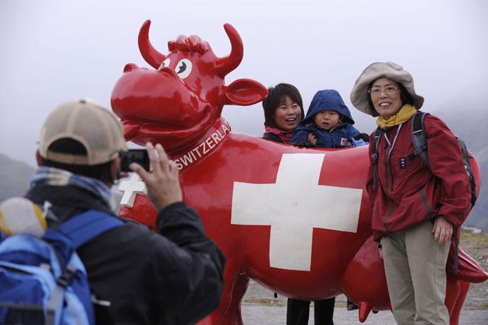 Suíça, Zermatt | Turistas japoneses posam para foto com uma das típicas esculturas de vacas. 2011.07.19 |