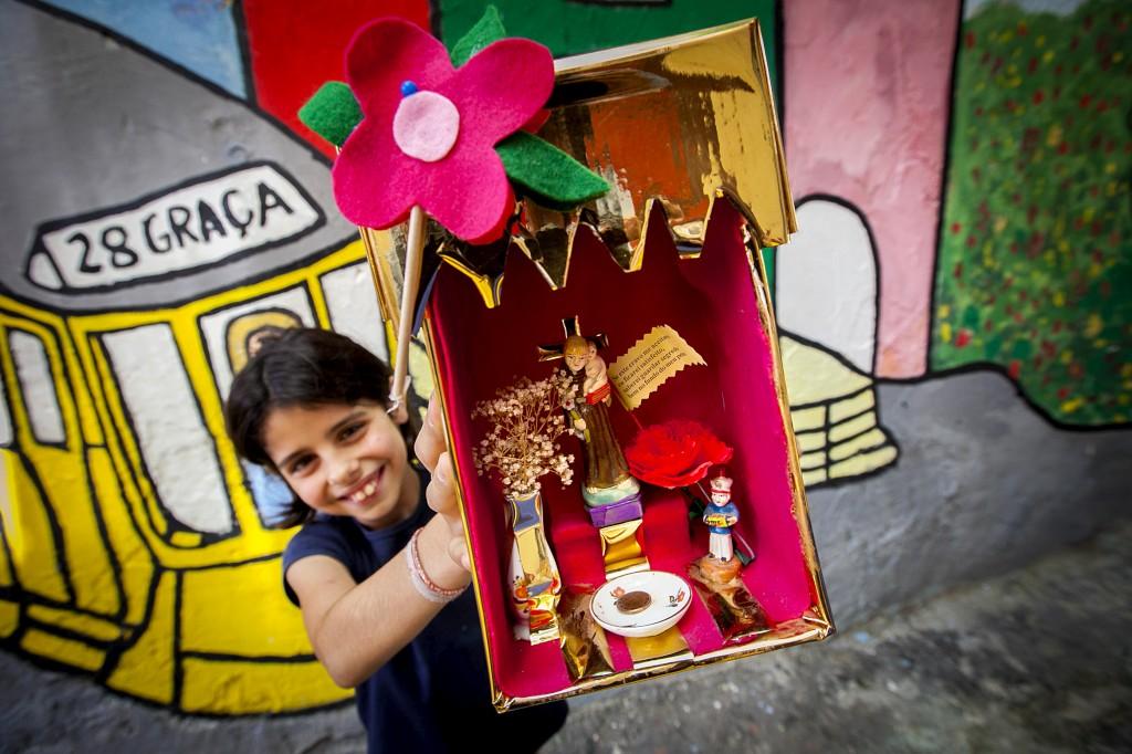 A receita: uma caixa de cartão, um napperon, um prato para o tostão, as velas, uma jarra de flores e o santo