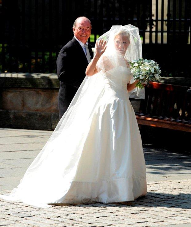 A noiva chega acompanhada pelo pai, Mark Phillips, num vestido em seda marfim, desenhado por Stewart Parvin, e sapatos Jimmy Choo.