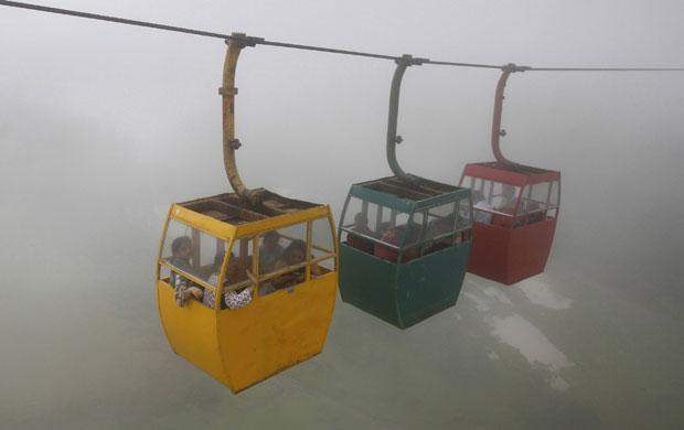 Índia, 30.07.2011 | Turistas num teleférico envolto pelas nuvens da monção na ligação ao monte Saputara.
