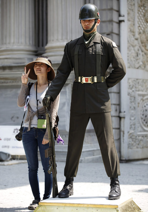 Turquia, Istambul, 31.07.2011| Uma turista sul-coreana posa ao lado de um soldado turco da guarda do palácio-museu Dolmabahce.