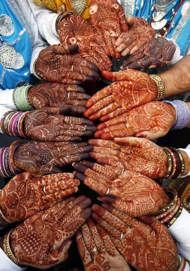 Índia, Chandigarh, 2.08.2011 | As mulheres de um grupo de dança tradicional mostram as mãos decoradas com hena antes da sua performance no festival Teej, que celebra o advento da monção e durante o qual seguidoras do hinduísmo fazem jejum e rezam pela saúde e longa vida dos seus maridos