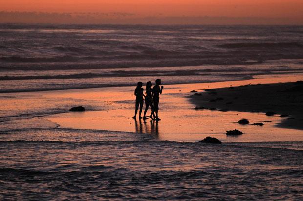EUA, Califórnia, 1.08.2011 | Uma pausa para brincar e refrescar ao pôr-do-sol numa praia de Cardiff