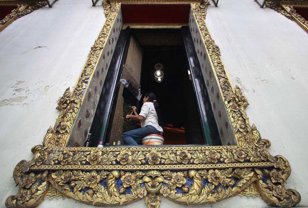 Tailândia, 04.08.2011 | Uma pintora trabalha no restauro do mural de uma janela do templo de Wat Pho (Wat Phra Chetuphon Vimolmangklararm Rajwaramahaviharn) em Banguecoque, alvo de um projecto de renovação.