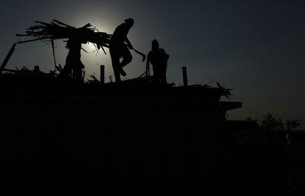 Indonésia, 04.08.2011 | Trabalhadores carregam cana de açúcar para um camião em Solo, Java.