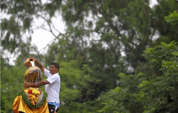 Nepal, 04.08.2011 | Um crente hindu despeja leite sobre a estátua do deus-cobra Naga em Katmandu, durante o festival Nag Panchami, em que são veneradas cobras.