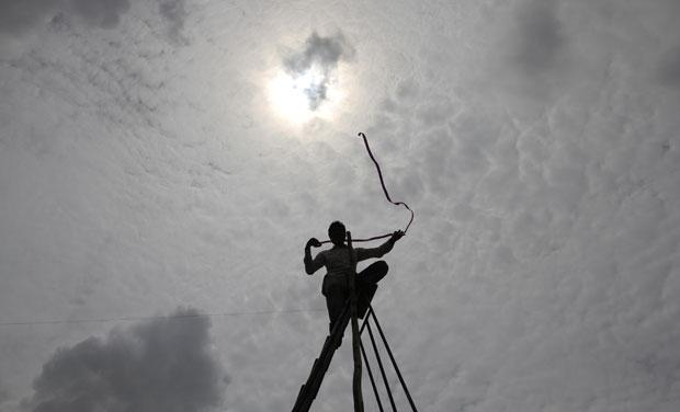 Índia, 04.08.2011 | Um trabalhador instala cabos de televisão sob as nuvens da monção, em Ahmedabad
