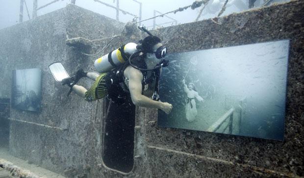 EUA, Florida, 04.08.2011 | Um mergulhador examina fotografias do austríaco Andreas Franke em exposição submarina num recife artificial do santuário marinho de Florida Keys. A mostra inclui uma dúzia de imagens criadas propositadamente para exibição aquática.