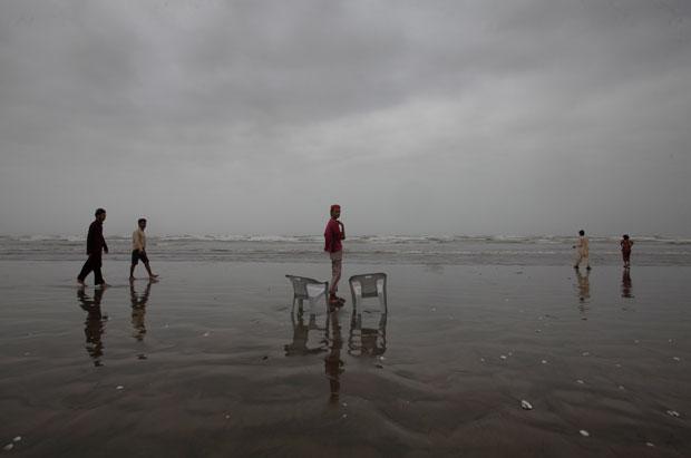 Paquistão, Karachi, 06.08.2011 | As nuvens da monção aproximam-se enquanto o alugador de cadeiras de praia pensa no seu negócio.