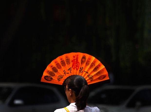 Pequim, 08.08.2011 | A arte de usar um leque com elegância para proteger o rosto do sol num quente dia de Pequim
