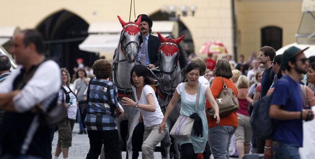 República Checa, 08.08.2011 | Turistas japoneses em fuga, assustadas com a carruagem que cruza a praça velha de Praga.