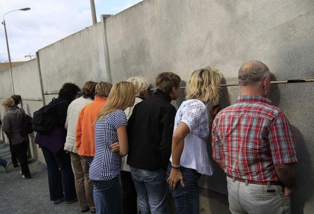 Alemanha, Berlim, 09.09.2011 | A espiar por uma abertura numa parte conservada do Muro de Berlim no memorial da Bernauer Strasse. A 13 de Agosto, passam 50 anos sobre a construção desta fortificação que dividiu a capital alemã.