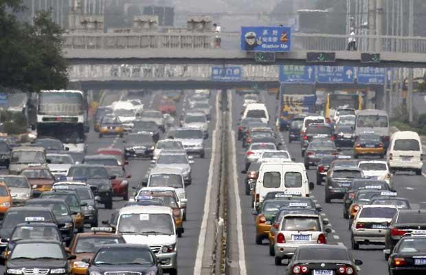 China, Pequim, 12.08.2011 | Peões atravessam uma ponte sobre o mar   de automóveis que crescentemente invade a capital chinesa. A venda   de carros continua em alta e as bicicletas vão sendo deixadas de lado.