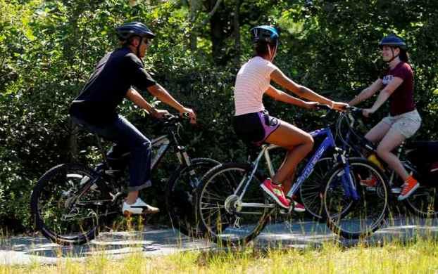 Massachusetts, 23 de Agosto de 2011 Uma ciclista anónima sorri ao Presidente dos Estados Unidos da Américae à sua filha Malia, durante um passeio de bicicleta em Martha's Vineyard