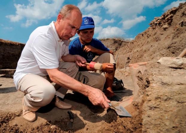 Rússia, 10 de Agosto de 2011 O primeiro-ministro russo, Vladimir Putin, desenterra um artefacto, guiado por um aluno de arqueologia numa escavação na península de Taman, no sul da Rússia