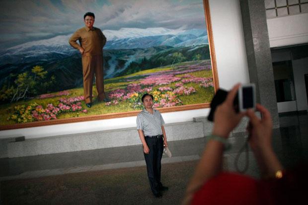 Coreia do Norte, 29.08.2011 | Um turista chinês posa para uma fotografia com um retrato do líder norte-coreano Kim Jong-il como cenário, num auditório da cidade de Rason, a nordeste de Pyongyang.