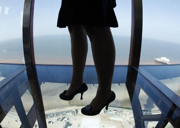 Reino Unido, Blackpool, 01.09.2011 | Uma mulher experimenta o passeio aéreo - um piso em vidro no topo - estreado na Blackpool Tower. A torre reabriu após dez meses de obras para restauro e inclusão de novas atracções.