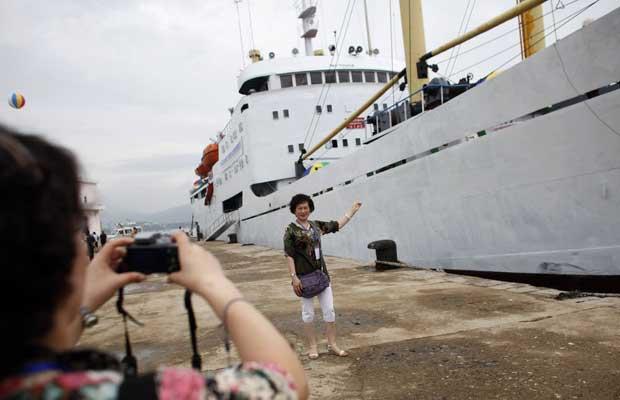 Turistas chinesas a guardarem recordações do cruzeiro, em Rason.