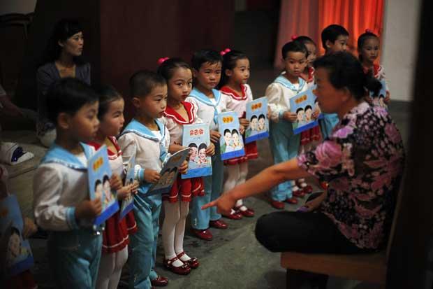 Pequenos artistas a receberem instruções do seu professor numa escola de Rajin.