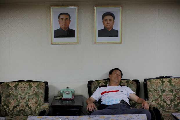 Um turista chinês dorme sob os retratos (omnipresentes na Coreia do Norte) do