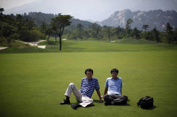 Dois turistas chineses descansam na relva de um campo de golfe (encerrado) no monte Kumgang.