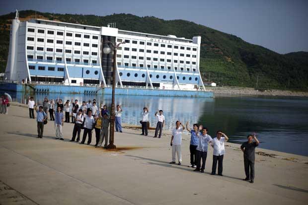 Representantes das autoridades norte-coreanas despedem-se dos turistas no porto de Kumgang.