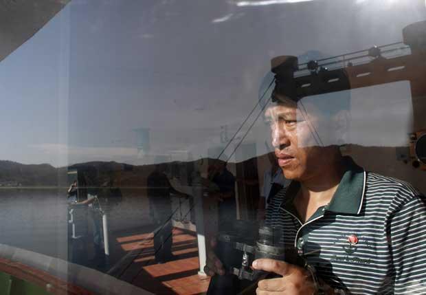Um tripulante do cruzeiro observa o porto de Kumgang.