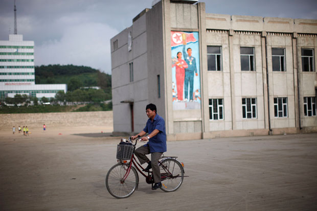 A pedalar junto ao edifício coberto de propaganda política em Rason.