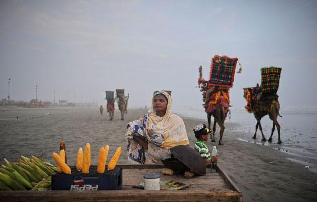 Paquistão, Carachi, 09.09.2011 | Junto à praia, Sughra vende milho assado enquanto os camelos, destinados a passeios, passam.